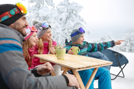 Boy showing something in distance to his family in cafe on ski terrain