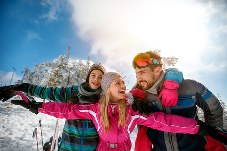 Happy family laughing and enjoying in winter vacations together on the mountain Archivio Fotografico
