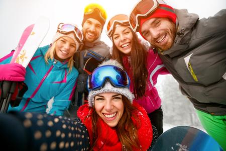 happy friends having fun on winter hodays. Snowbarders and skiers group team friendship making selfie Zdjęcie Seryjne