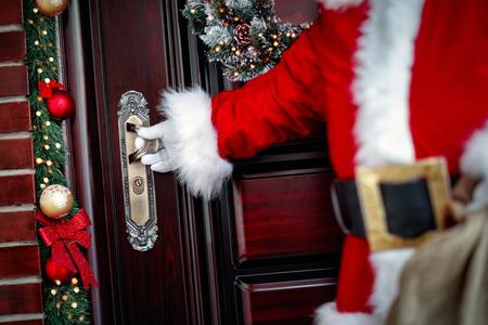 gloved hands of Santa Claus open the door close up