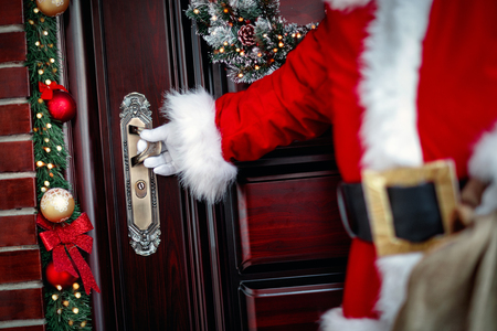 gloved hands of Santa Claus open the door close up