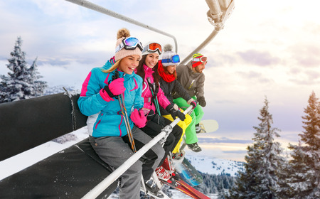 group of cheerful friends are lifting on ski-lift for skiing in the mountains Zdjęcie Seryjne