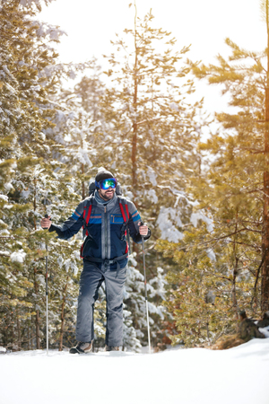 Smiling hiker with backpack trekking in forest. Winter hiking Stock Photo