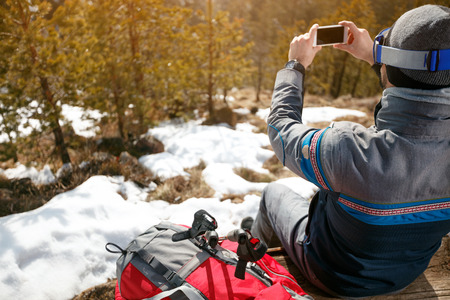 young man on hiking and photography mountain landscape with mobile phone Stock Photo