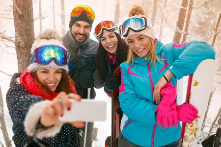 smiling snowboarders or skiers making selfie in fog forest Zdjęcie Seryjne