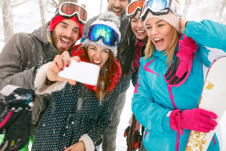 smiling young snowboarders or skiers making selfie in fog forest Banque d'images