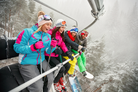smiling friends skiers and snowboarders on ski lift for skiing in the mountains