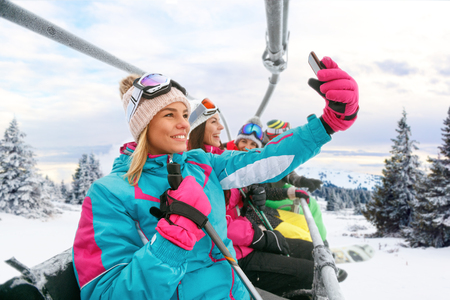 young friends skiers enjoying in the slopes and making selfie