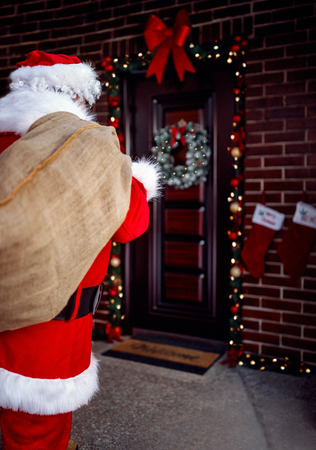 Santa Claus carrying bag with present for children in Christmas night Stock Photo