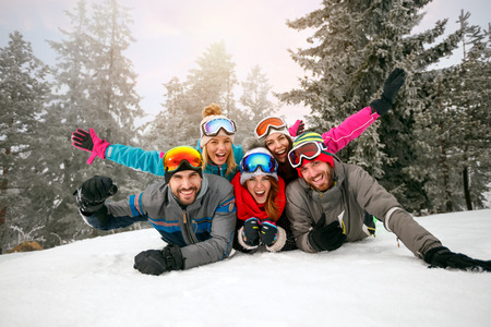 friends on winter holidays – Happy skiers lying on snow and having fun