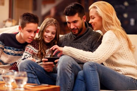 Family having fun on digital tablet for Christmas time 版權商用圖片 - 91000999