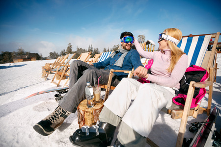smiling man and woman in love enjoying together in sun at mountains in winter