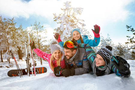 Happy smiling family enjoying winter vacations in mountains on snow