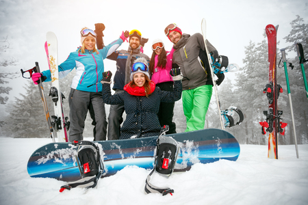 cheerful friends skiers and snowboarders having fun on snowbound winter forest