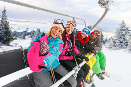 cheerful friends skiers enjoying in the slopes at winter vacations and making selfie on mountain