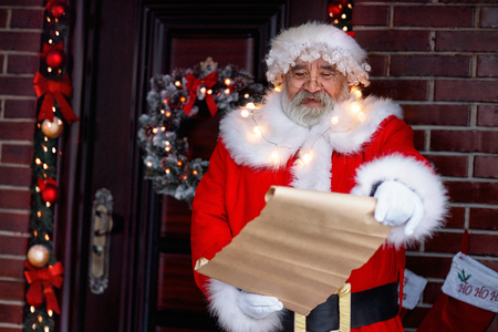 Smiling Santa Claus holding scroll paper Stock Photo