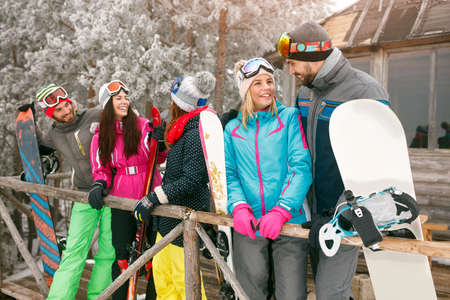 cheerful friends spend winter holidays at mountain cottage