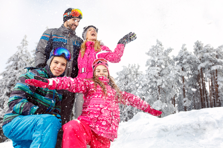 Children with parents in snowy nature at winter vacation in mountain 写真素材