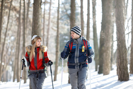 Couple of hikers in winter look at each other while hiking together