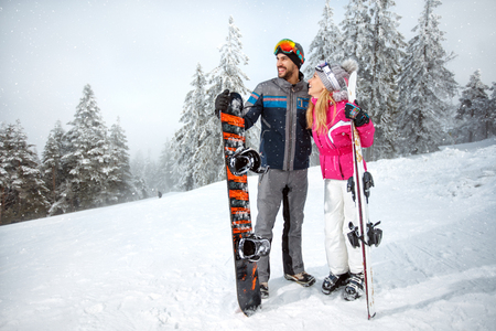 Smiling sportsman and sportswoman on skiing holding ski equipment on ski terrain
