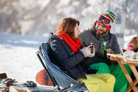Skiers couple in love drinking and talking in cafe on skiing