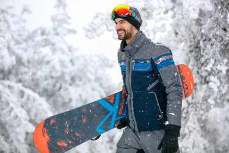 Male snowboarder with snowboard going to ski terrain Banque d'images