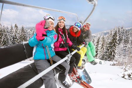 Young female making selfie with friends in ski lift