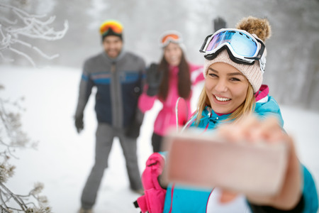 Cute female making selfie on skiing