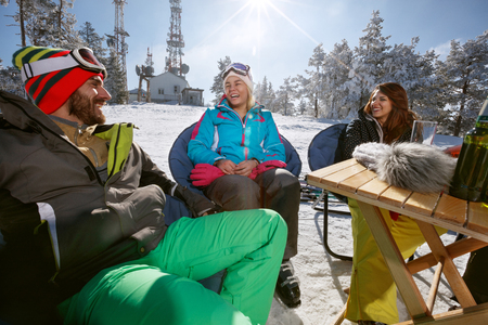 Happy male and female skiers talking and smiling in cafe on ski terrain