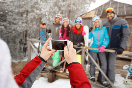 Close up of cell phone and hands taking photo of skiers