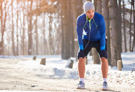 Male athlete make pause from running in snowy nature Stock fotó