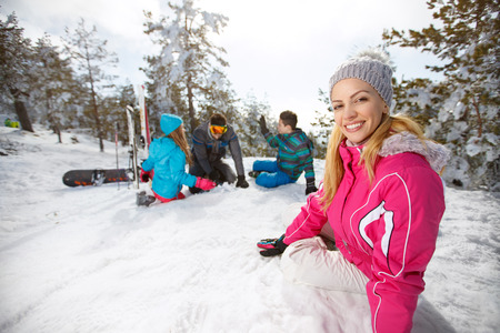 Young woman with family enjoying on snow on skiing