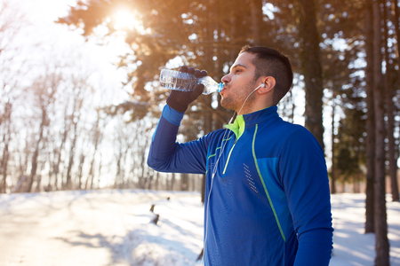 Male refreshes with water after running in woods  Stock Photo