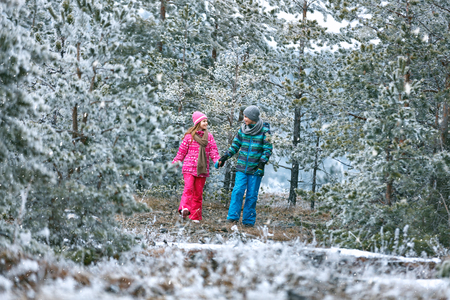 Male and female child walking together in snowy nature in mountain