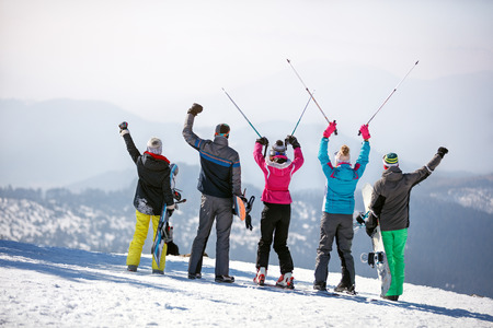 Back view of group skiers with hands and ski sticks up in mountain