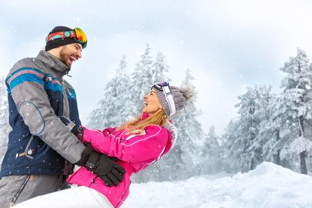 Cheerful man and woman having fun in snowy nature on mountain Stock fotó