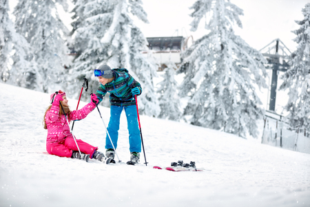 Boy helps to young girl to get up from snow with skis Banque d'images