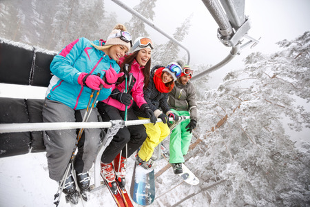 Young skiers in ski lift happy together