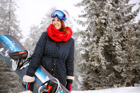 Girl hold snowboard and go to skiing in mountain Stock Photo - 93560979