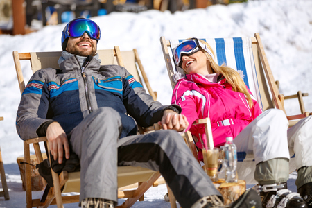 Smiling couple on break from skiing enjoy on sun in ski loungers  Banque d'images