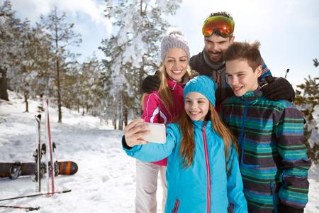 山でスキーに家族とセルフを取る女の子