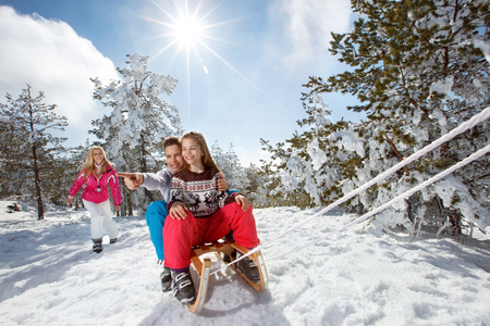 Children enjoying on sleds on winter holiday with mother Banque d'images