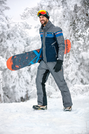 Man with snowboard at winter holiday in mountain