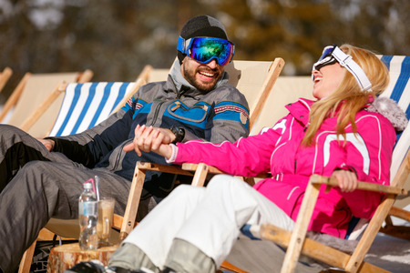 smiling man and woman enjoying together in sun at mountains in winter