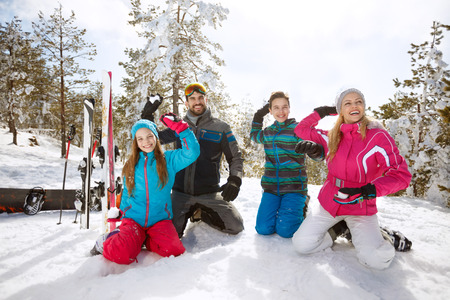 Happy family making snow balls on skiing in mountain