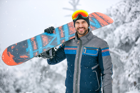 Happy man with snowboard on ski terrain Stock Photo