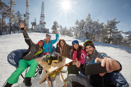 Skiers in cafe outdoor taking selfie with cell phone