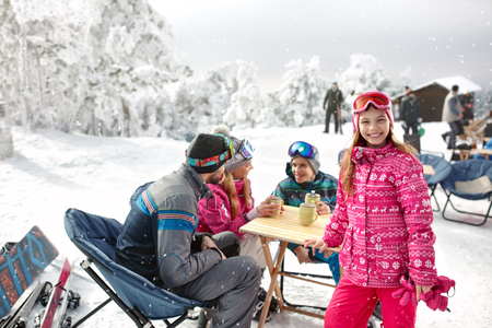 Smiling young girl with family in cafe on ski terrain enjoy Banque d'images