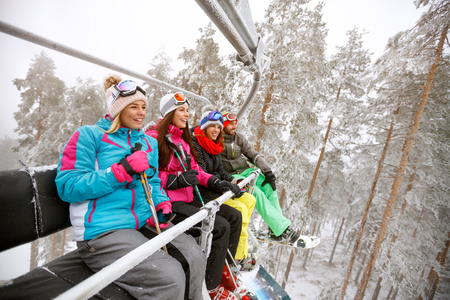 Young women and man in ski lift together Banque d'images