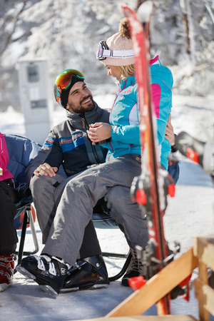 Woman on skiing in mountain  sitting in mans lap